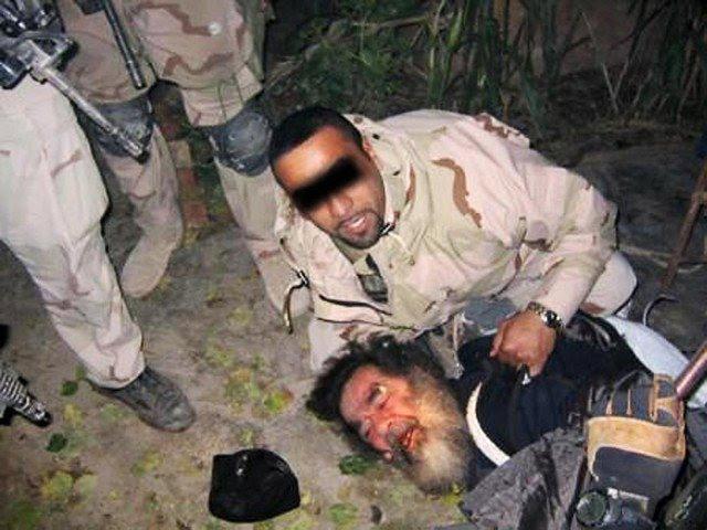 Saddam Hussein sendo arrastado para fora do seu esconderijo